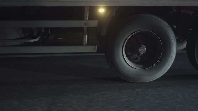 vídeos de stock e filmes b-roll de close-up of a semi-trailer wheel in motion on the highway at night. - vista lateral