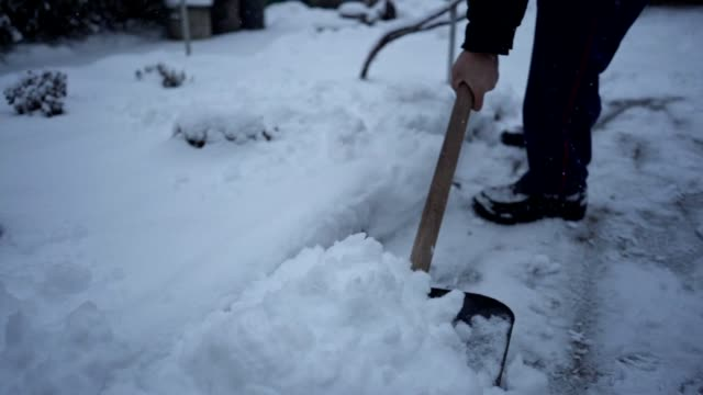 close-up of a senior adult shoveling snow in his yard - spade stock videos & royalty-free footage