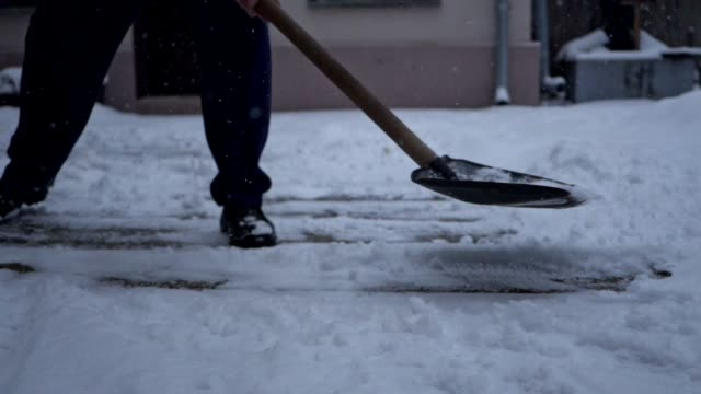 close-up of a senior man shoveling the snow from his back yard - spade stock videos & royalty-free footage