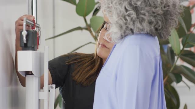 Gros plan d'une femme Senior pesée au cours de la visite médicale