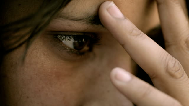 stockvideo's en b-roll-footage met close-up of a serious, young woman thinking deeply. - verdriet