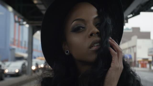vídeos de stock, filmes e b-roll de closeup of a sexy african american woman in her twenties posing beneath the train tracks in brooklyn, nyc - 4k - passagem subterrânea via pública