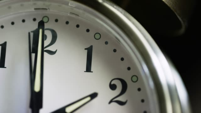 close-up of a silver-colored, metal, retro-style, analog alarm clock almost striking 2:00 - timer stock videos & royalty-free footage
