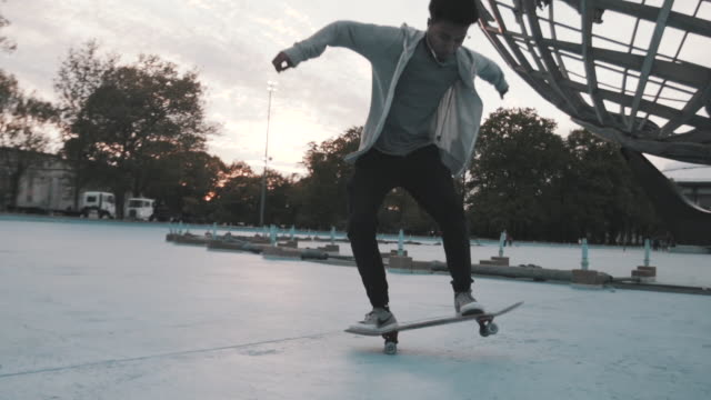 vídeos de stock, filmes e b-roll de a closeup of a skateboarding crashing at sunset in flushing, queens - slow motion - flushing meadows corona park
