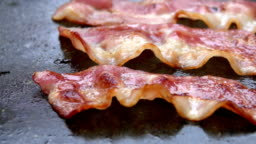 Close-up of a slice of bacon fried on grill