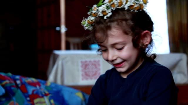 vidéos et rushes de gros plan d'un enfant souriant, portant la couronne de fleurs sur la tête - série d'émotions