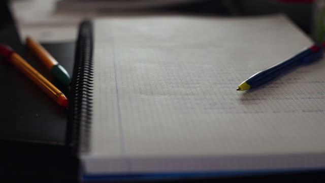 vídeos de stock e filmes b-roll de close-up of a spiral notebook and a pen on the living room table - caneta