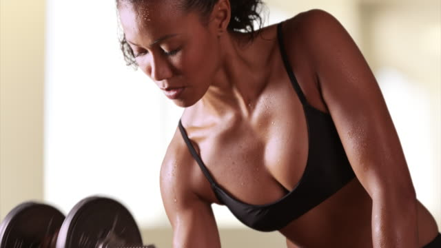 closeup of a strong a mixed race woman athlete lifting weights - arm curl stock videos and b-roll footage