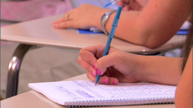 close-up of a student's hand taking notes while sitting in class. - unrecognisable person stock videos & royalty-free footage