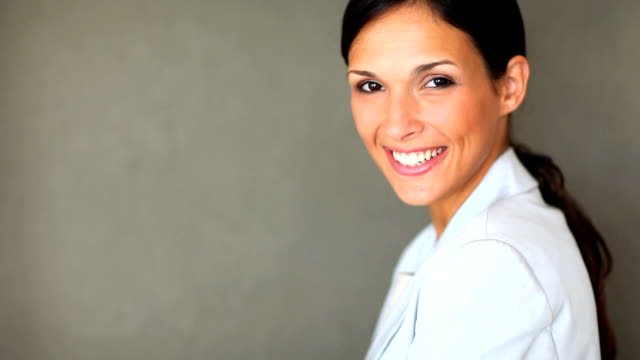 close-up of a successful woman against gray background - toothy smile stock videos & royalty-free footage