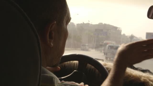 vídeos y material grabado en eventos de stock de close-up of a taxi driver gesturing whilst driving and talking to a passenger, cairo, egypt. - taxista