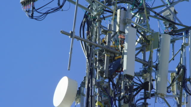 close-up of a technician assembling a cell phone tower on a clear, sunny day - tower stock videos & royalty-free footage