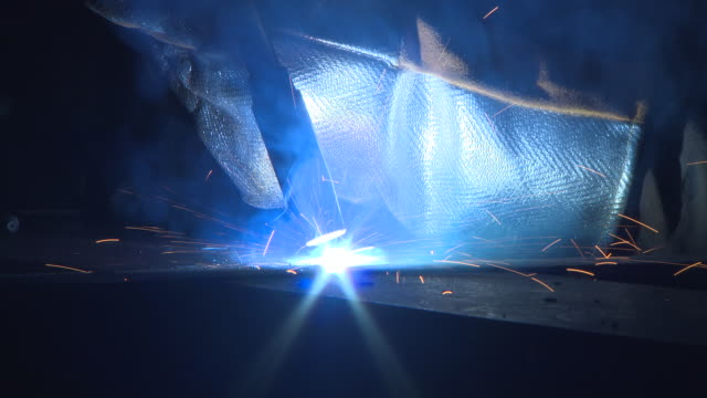 vídeos de stock, filmes e b-roll de close-up of a tool emitting intense blue light being used to weld at a shipyard in glasgow, scotland. - soldador