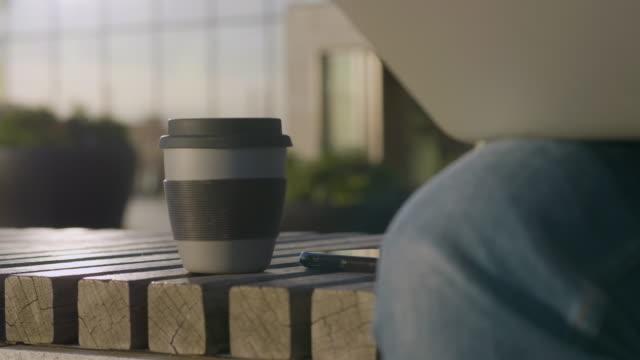 närbild av en travel mug bredvid en man som arbetar på språng - kaffe dryck bildbanksvideor och videomaterial från bakom kulisserna