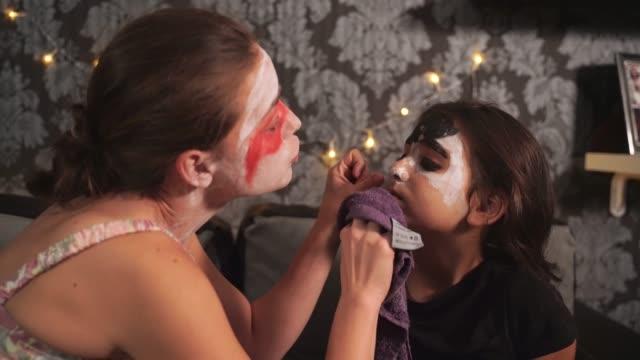 Nahaufnahme einer Frau, die Reinigung des kleinen Mädchens Halloween Gesicht malen mit einem Handtuch