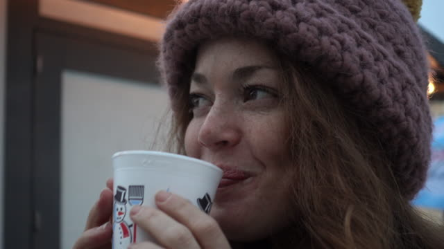 Close-up of a woman drinking a hot drink from a cup
