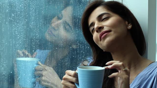vídeos de stock e filmes b-roll de close-up of a woman having a cup of tea and dreaming  - sonhar acordado