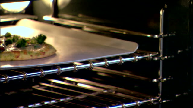 close-up of a woman removing a cooked pizza from the oven. - oven mitt stock videos and b-roll footage