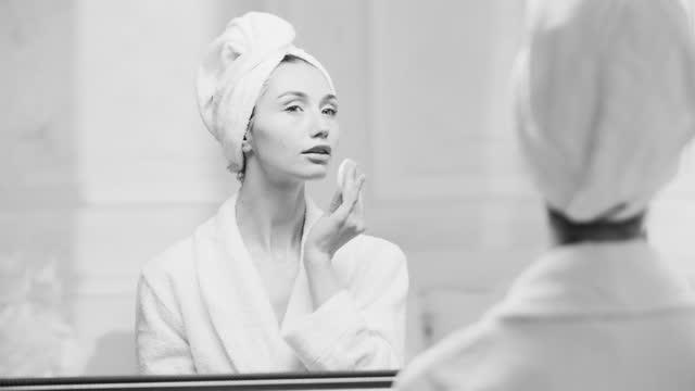 vidéos et rushes de gros plan d'une femme assise dans une robe blanche devant un miroir et nettoyant sa peau avec un coton. vidéo en noir et blanc. - soin du corps