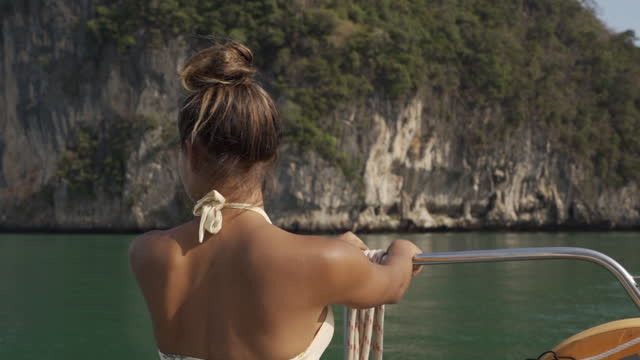 close-up of a woman standing in a boat admiring a rocky ocean water view with sunlight, breezes, and gently rippling water - nusa penida & lombok, bali - bali stock videos & royalty-free footage