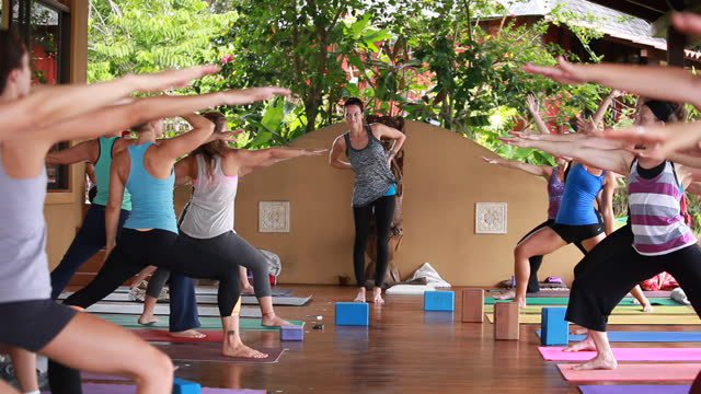 close-up of a woman teaching yoga and we zoom out to reveal an outdoor deck with women practising yoga and colourful yoga attire and colourful mats surrounded by lush vegetation - kelly mason videos stock videos & royalty-free footage