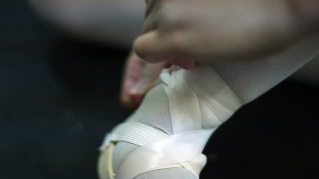 closeup of a woman tightly tying her toe shoes with pink ribbons. - ballet shoe stock videos and b-roll footage