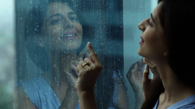 Close-up of a woman watching rain