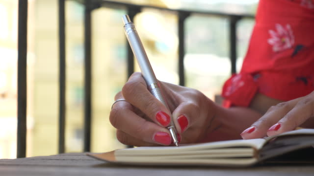 Close-up of a woman writing in a journal diary traveling in a luxury resort town in Italy, Europe. - Slow Motion