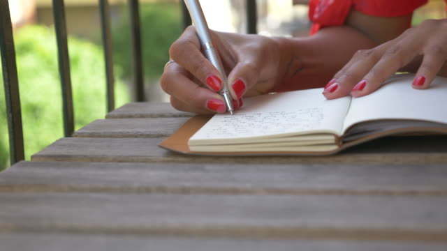 close-up of a woman writing in a journal diary traveling in a luxury resort town in italy, europe. - slow motion - pen stock videos & royalty-free footage