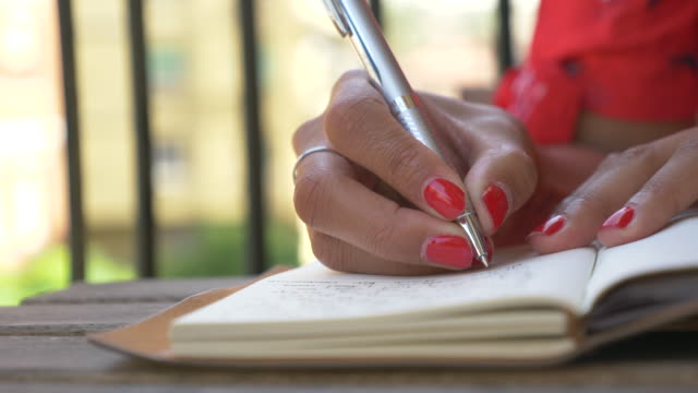 close-up of a woman writing in a journal diary traveling in a luxury resort town in italy, europe. - slow motion - diary stock videos & royalty-free footage