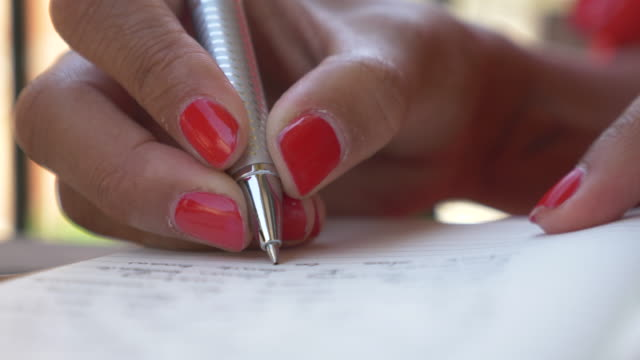 vidéos et rushes de close-up of a woman writing in a journal diary traveling in a luxury resort town in italy, europe. - slow motion - écrire