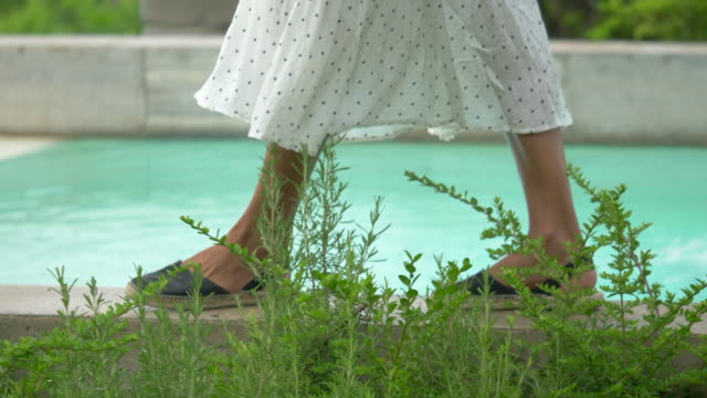 closeup of a woman's feet and sandals at a pool traveling at a luxury resort in italy, europe. - schuhwerk stock-videos und b-roll-filmmaterial