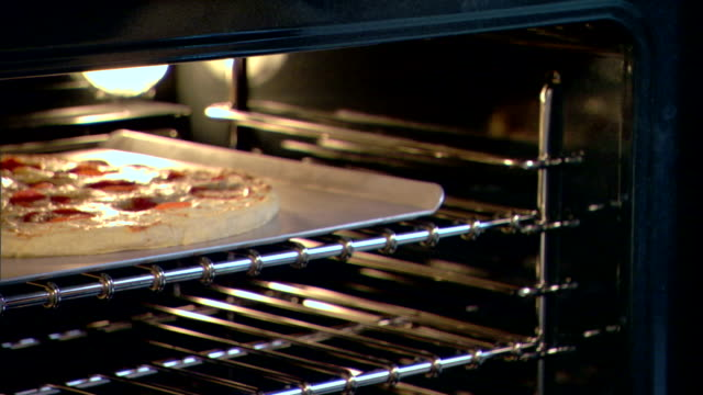 close-up of a woman?s hand removing a cooked pizza from the oven. - oven mitt stock videos and b-roll footage