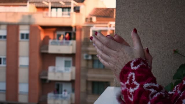 a close-up of a woman's hands as she is clapping from her balcony - community stock videos & royalty-free footage