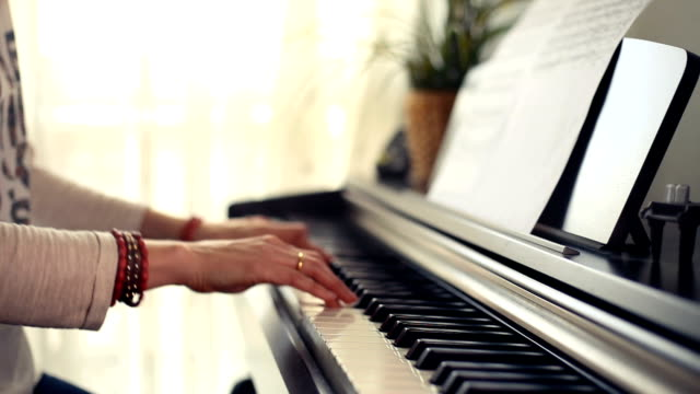stockvideo's en b-roll-footage met close-up of a woman's hands playing a delicate tune on the piano - una sola mujer