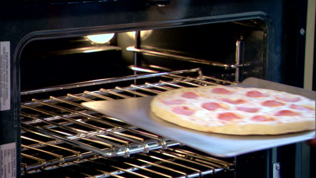 close-up of a woman?s hands putting a frozen pizza in the oven. - oven mitt stock videos and b-roll footage