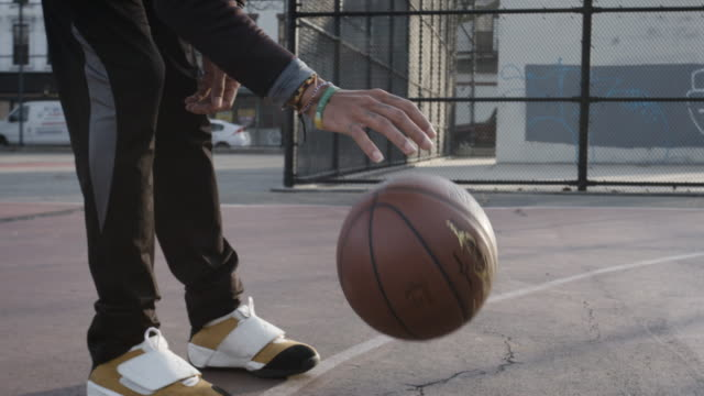 stockvideo's en b-roll-footage met closeup of a young, black, candid man dribbling a basketball in bedford stuyvesant, brooklyn - 4k - dribbelen