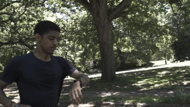 vidéos et rushes de a closeup of a young black man's legs and feet as he exercises by running through a park. - seulement des jeunes hommes