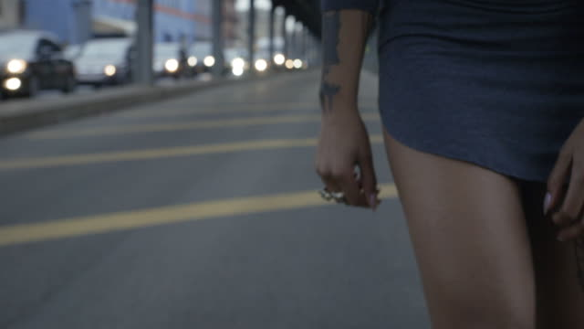 Closeup of a young, black woman's tattooed legs on the streets of Brooklyn, New York City - 4k