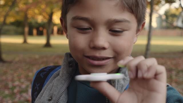 公園で人気のあるおもちゃで遊ぶ少年のクローズ アップ - 自閉症点の映像素材/bロール