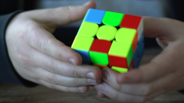 stockvideo's en b-roll-footage met a close-up of a young boy solving a cube puzzle in less than a minute. - oplossen