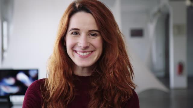 vídeos de stock e filmes b-roll de close-up of a young businesswoman smiling in office - caucasian ethnicity