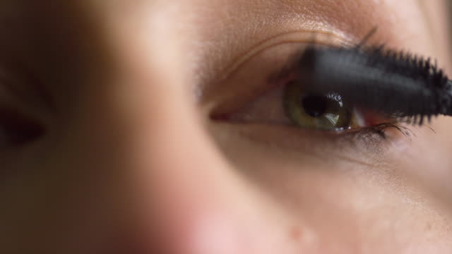 Close-Up of a Young Caucasian Woman Using a Mascara Wand to Apply Mascara Makeup to Her Eyelashes