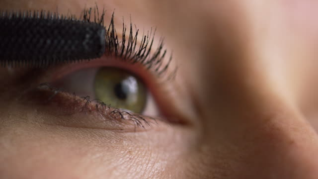 close-up of a young caucasian woman using a mascara wand to apply mascara makeup to her eyelashes - mascara stock videos & royalty-free footage