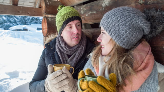 close-up of a young couple at a log cabin drinking hot tea in winter - cappotto invernale video stock e b–roll