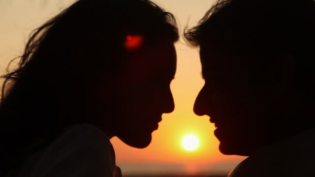 Close-up of a young couple romancing on the beach