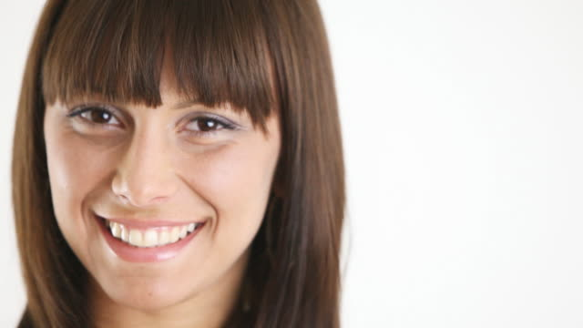 close-up of a young girl smiling against white background - bangs stock videos and b-roll footage