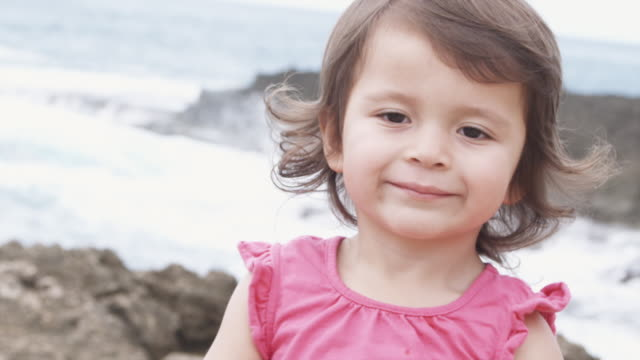 close-up of a young girl smiling on a beach - maglietta senza maniche video stock e b–roll
