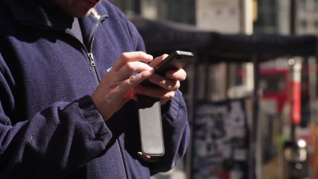 close-up of a young man using a smart phone in a london street, uk. - communication stock videos & royalty-free footage