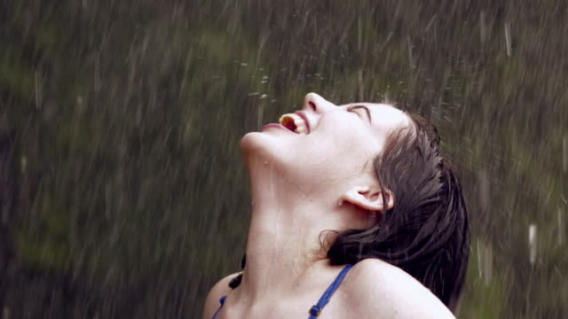 close-up of a young woman bathing in rain, delhi, india - regen stock-videos und b-roll-filmmaterial
